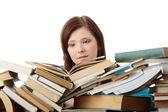 Ung kvinna sitter bakom böcker — Stockfoto