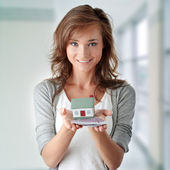 Woman holding euros bills and house model — Foto Stock