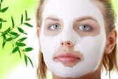 Jonge vrouwelijke gezicht met klei masker — Stockfoto