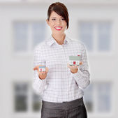 Young businesswoman holding two house models — Stock Photo