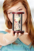 Teen woman holding hourglass — Stock Photo