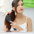 Beautiful young woman brushing her hair — Stock Photo #5065168