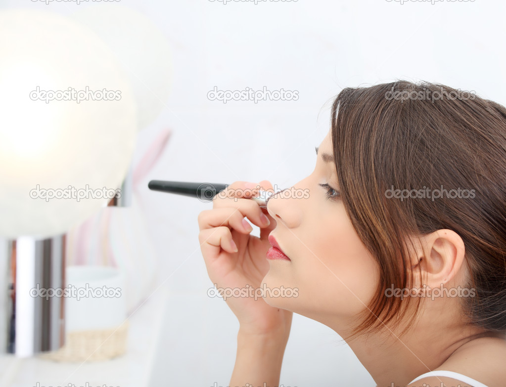 Portrait of attractive young adult woman applying blusher in her bathroom — Stock Photo #5065135
