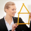 Beautiful businesswoman with house model - Stock Photo