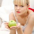 Beautiful woman on couch holding an apple. — Stock Photo #5340580