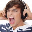 Foto de Stock  : Young man's singing with headphones.