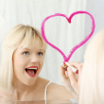 Young beautiful woman drawing big heart on mirror. — Stock Photo