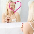 Young beautiful woman drawing big heart on mirror. — Stock Photo #5340917