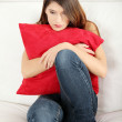Sad woman's sitting on couch and squeezeing pillow. — Stock Photo #5340928