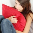 Sad woman's sitting on couch and squeezeing pillow. — Stock Photo