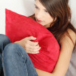Sad woman's sitting on couch and squeezeing pillow. — Stock Photo #5340933