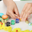 Stock Photo: Young girl is making easter decoration
