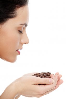 Woman holding asnd smelling coffee beans