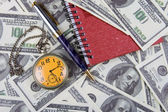 Pocket watch, notebook and pen on a stack of dollars — Stock Photo