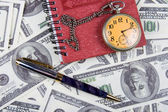 Pocket watch, notebook and pen on a stack of dollars, reflecting time and m — Stock Photo