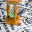 Sandglass on a stack of dollars — Stock Photo