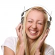 A beautiful young and happy woman listen music — Stock Photo #4302324