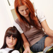 Two young and beautiful girls in room reading magazine - Stock Photo