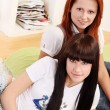 Two young and beautiful girls in room - 
