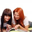 Two young and beautiful girls in room reading magazine — Stock Photo #4302695