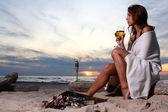 Krásná mladá žena, pití vína na pláži — Stock fotografie