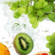 Fruits dropped into water - Stockfoto