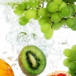 Stock Photo: Fruits dropped into water