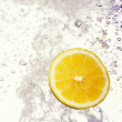 Lemon dropped into water — Stock fotografie