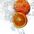 Oranges dropped into water - Stock Photo