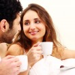 Young couple having breakfast in bed - Stock Photo