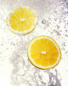 Lemons dropped into water — Stock Photo