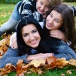 Young famiy in autumn park — Stok fotoğraf