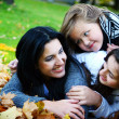 Young famiy in autumn park — Stock Photo