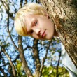 Attractive blonde guy behind a tree — Stock Photo #5019034