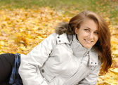 Girl lying in autumn park — Stockfoto
