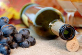 Empty bottle, cork, grapes and wineglass. — Stock Photo