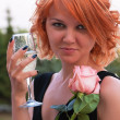Beautiful woman with pink rose drinking champagne — Stock Photo