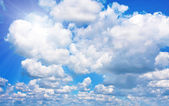 Background of blue cloudy sky and sun — Foto de Stock