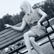 Beautiful young blonde woman sitting on bench — Stock Photo #4784869
