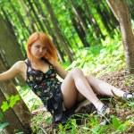 Beautiful woman sitting on the stump — Stock Photo #5218752