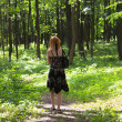 Ginger-haired woman walking in forest — Stock Photo