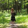 Ginger-haired woman walking in forest — Stock Photo #5285146