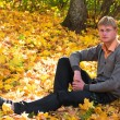 Young man in autumn forest — Stock Photo