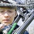 Woman repairing bicycle outdoors - Stock Photo
