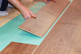 Worker installing new laminate flooring — Stock Photo