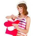 Cute girl cutting valentine heart — Stock Photo