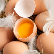 Eggs and feathers at hay — Stock Photo