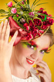 Beautiful young woman with creative flower cap — Stock Photo