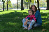 Mother and daughter are sitting at the park — Stock Photo