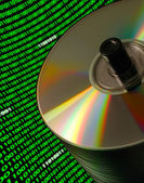 Stack of CD/DVD disks with a curved field of binary code — ストック写真